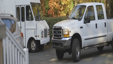 Compressed image of a white van and white truck parked in driveway