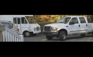 Wide frame image of a white van and white truck parked in driveway
