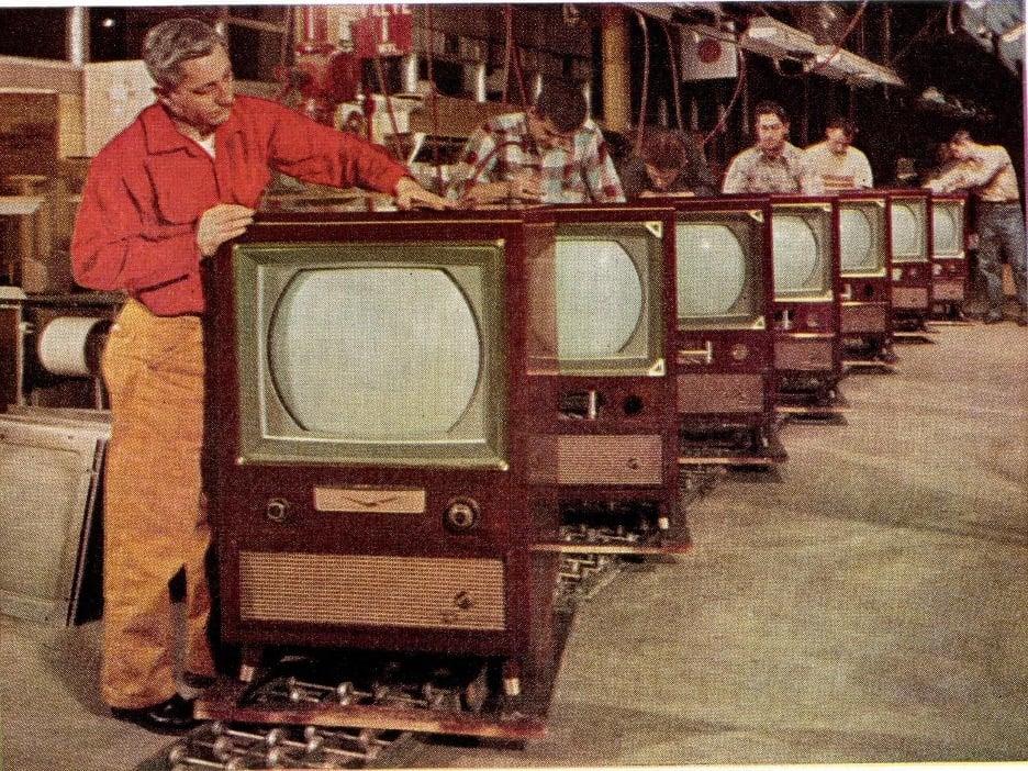 tv repair man examining a tube televison